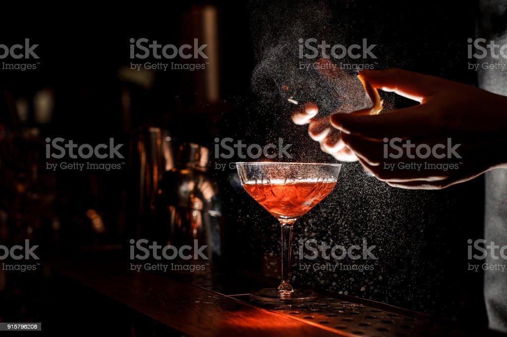 Barkeeper spritzt eine Orangenschale im Cocktailglas – Foto