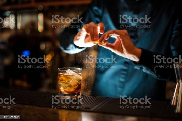 Bartender sprinkling orange peel juice into a cocktail glass picture id962125592?b=1&k=6&m=962125592&s=612x612&h=1of2vcuecfvhu3llp xgc2mpldenotz1ybyzaektx14=