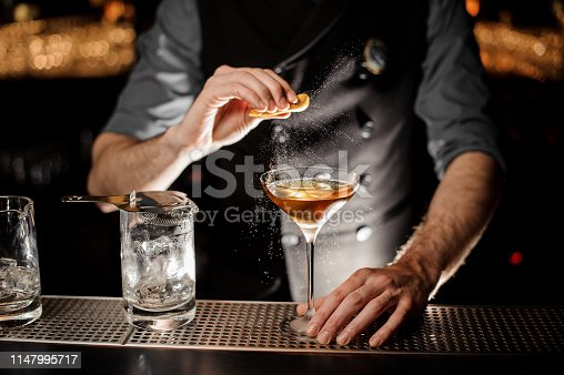 Male bartender in gray shirt squeezing fresh lemon rind in alcohol cocktail