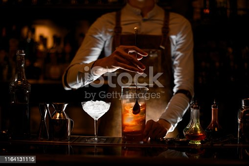 Male bartender in white shirt and leather apron stirring alcohol cocktail with a special bar spoon