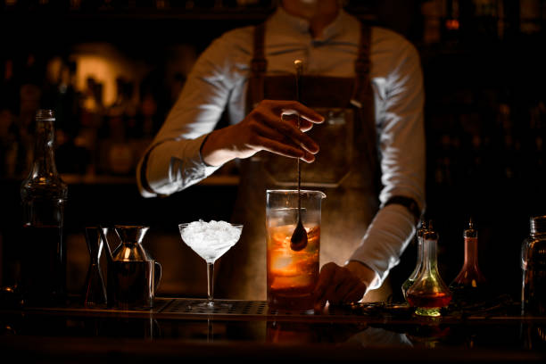 Bartender stirring alcohol cocktail with a spoon Male bartender in white shirt and leather apron stirring alcohol cocktail with a special bar spoon bartender stock pictures, royalty-free photos & images