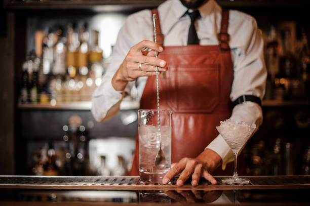 Bartender stirring an ice cubes in the cocktail Bartender in the white shirt and brown leather apron stirring an ice cubes in the cocktail on the bar counter bartender stock pictures, royalty-free photos & images