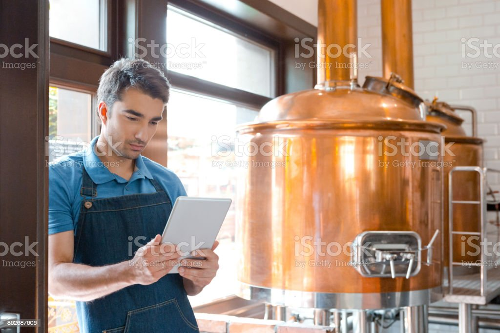 Bartender using a digital tablet in micro brewery Bartender standing in the pub and using a digital tablet. Copper vats in the background. Adult Stock Photo