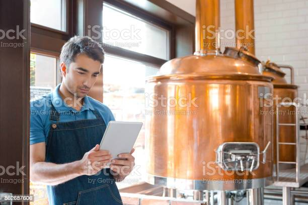 Bartender Using A Digital Tablet In Micro Brewery Stock Photo - Download Image Now
