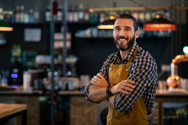 Bartender wearing apron and smiling stock photo