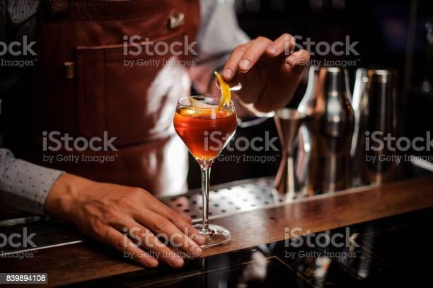 Bartender with glass and lemon peel preparing cocktail at bar picture id839894108?b=1&k=6&m=839894108&s=612x612&h=c6de5td5aedpmjzltzk1ulfldywbmsi62 lyrtw ryw=