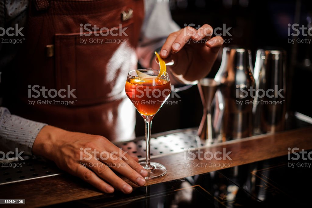 Bartender with glass and lemon peel preparing cocktail at bar - foto stock