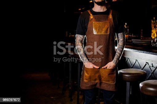 1003493404istockphoto Bartender with tattoo dressed in brown apron туфк ифк сщгтеук 989297672