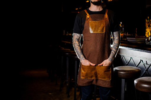 1003493404 istock photo Bartender with tattoo dressed in brown apron туфк ифк сщгтеук 989297672