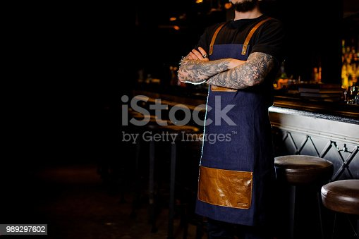 1003493404istockphoto Bartender with tattoo on hands dressed in blue and brown apron 989297602
