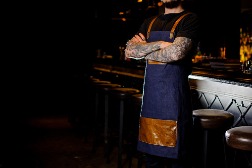1003493404 istock photo Bartender with tattoo on hands dressed in blue and brown apron 989297602