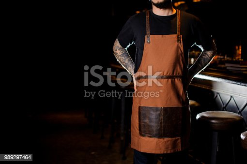 1003493404istockphoto Bartender with tattoo on hands dressed in brown apron 989297464