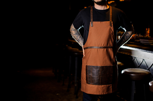 1003493404 istock photo Bartender with tattoo on hands dressed in brown apron 989297464