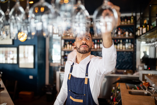 Mixed race barman working at the cafe. Bartender taking a wineglasses from the overhead rack at bar counter.