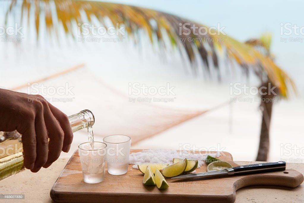 bartender's hand pouring tequila at a tropical Caribbean beach stock photo