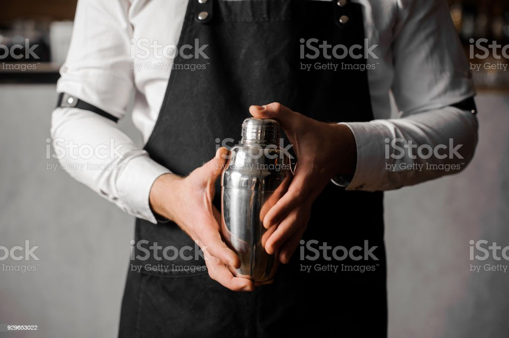 Bartenders hands holding a shaker against the bar counter stock photo