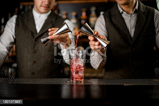 Two bartenders hold steel jiggers in their hands and pour drink into transparent glass with ice cubes