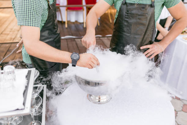 bartenders serve the cocktail in a large bowl with liquid nitrogen. row line of different alcoholic cocktails on a party. wedding day or birthday bartenders serve the cocktail in a large bowl with liquid nitrogen. row line of different alcoholic cocktails on a party. wedding day or birthday. liquid nitrogen stock pictures, royalty-free photos & images
