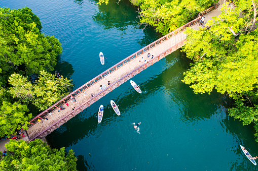 Barton Springs Austin Texas USA Aerial drone views above the Barton Creek Bridge as crowds of people walk across the bridge and Kayakers go under and swimmers swim in the cold refreshing waters fed by Cold Springs