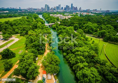 An Aerial Bird's Eye View of Austin Texas skyline cityscape in the background with Zilker Park to the left and Baton Springs Creek down below. A Clear spring water paradise view