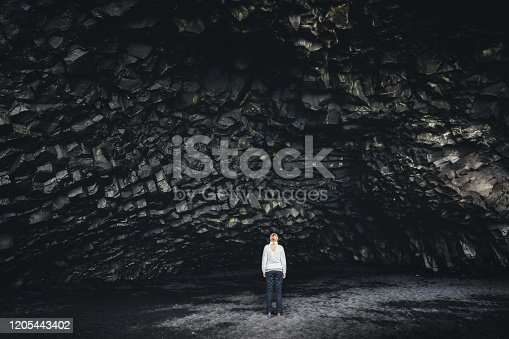 Woman standing in the basalt cave Halsanefshellir on the famous black-sand beach Reynisfjara.