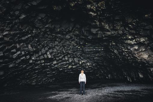 Woman standing in the basalt cave Halsanefshellir on the famous black-sand beach Reynisfjara.