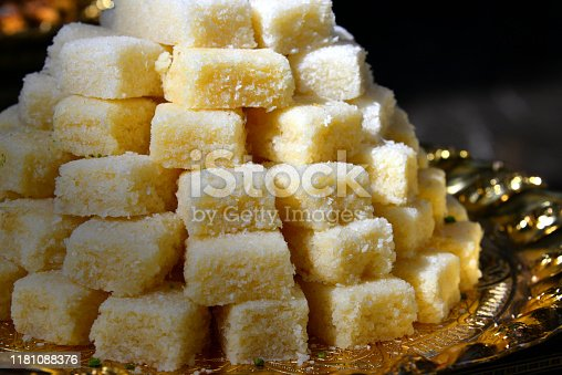 Riyadh, Saudi Arabia: pile of Basbousa cubes (aka Hareeseh / Nammoura / Semissa) - a traditional cake made from a semolina batter and sweetened with orange flower water syrup. Basbousa has been associated with many holidays and occasions such as the month of Ramadan to provide Basbousa for Iftar and before Suhoor.