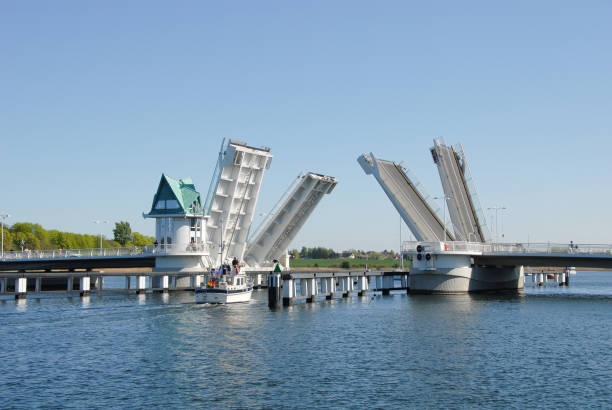 Bascule bridge Sailing boat under an opening bascule bridge bascule bridge stock pictures, royalty-free photos & images