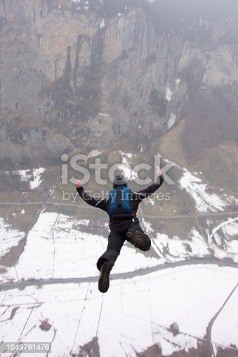 istock Base jumper launches off cliff in the Swiss alps 1049791476