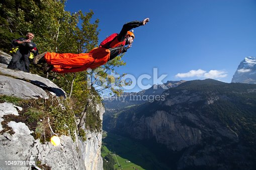 Base jumper launching off cliff