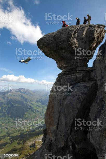 Photo of Base jumper/ wingsuiter launches off cliff in the Alps