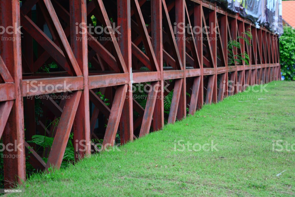 base of old iron structure of billboards in the city with green grass stock photo