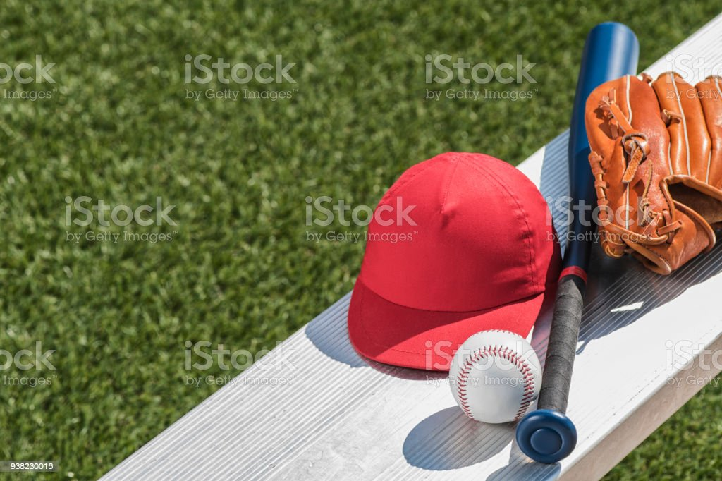 Looking down on a baseball, a red baseball cap, a brown leather glove...