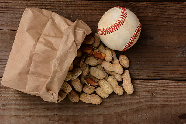 baseball and a bag with peanuts spilling out - peanut food stock photos and pictures