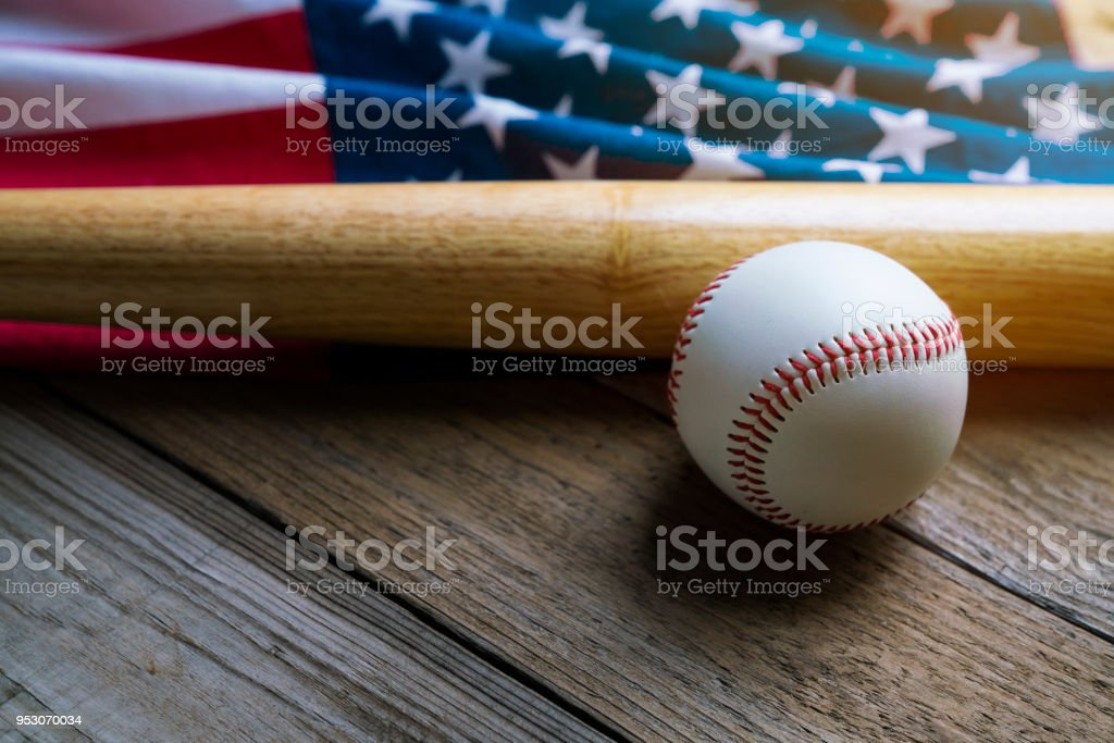 baseball and baseball bat with American flag in the background