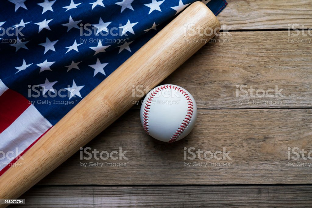 baseball and baseball bat with American flag on wooden table background stock photo