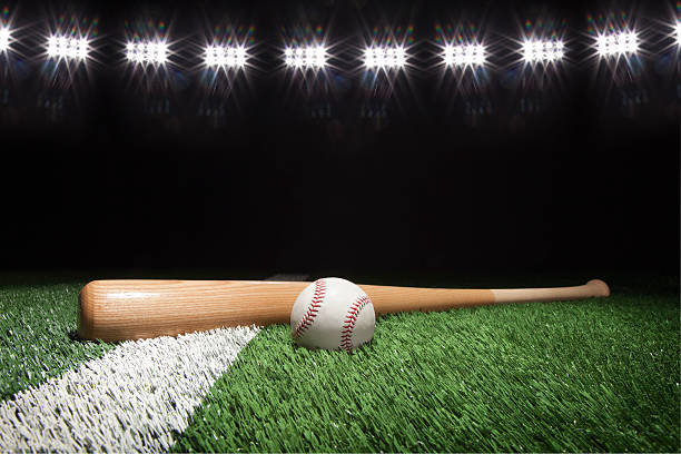 Baseball and bat at night under stadium lights stock photo