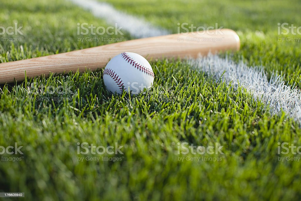 Baseball and bat on grass field with white stripe stock photo