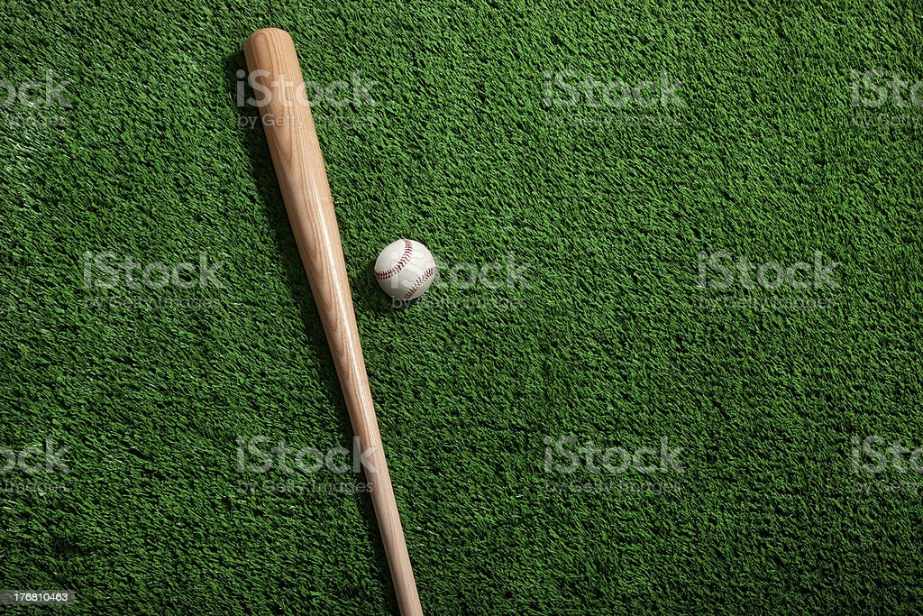 Baseball and bat on green grass stock photo