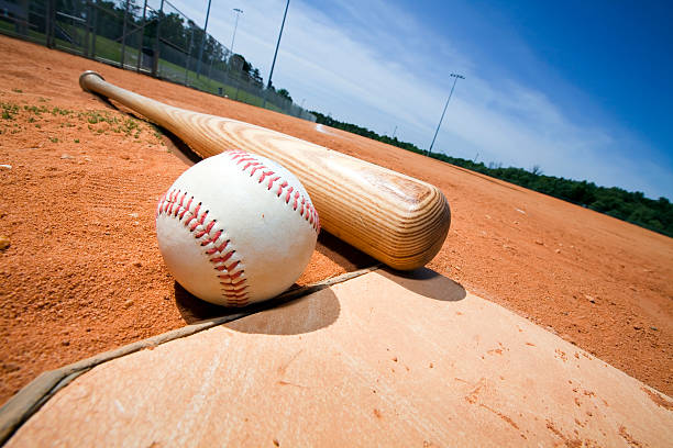 baseball and bat on home plate - softball stock photos and pictures