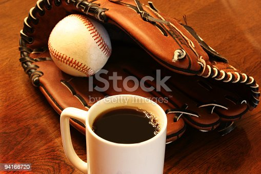 Baseball and leather ball glove with coffee cup on wooden table.