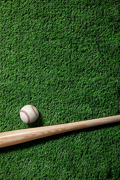 A baseball and wooden bat on artificial green grass stock photo