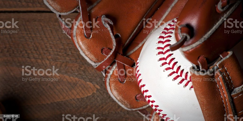 Photo of an Baseball ball and glove on wooden table. Studio shot