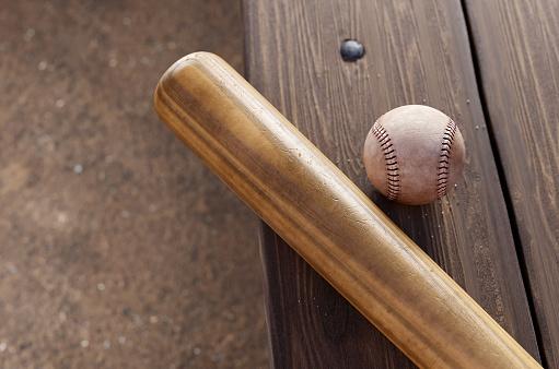 Baseball Bat, and ball on dugout bench.