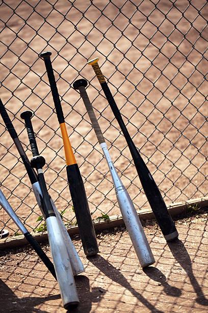 baseball schläger lehne dich gegen maschendrahtzaun während des spiels. - alu zaun stock-fotos und bilder