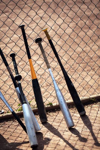 baseball-schläger an zaun lehnen. - alu zaun stock-fotos und bilder