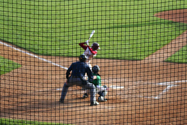 Baseball Batter Catcher Umpire Waiting for Pitch Baseball hitter waits for the next pitch - with catcher and umpire set for action. Deliberate shallow depth of field with players blurred beyond a protective net screen. netting stock pictures, royalty-free photos & images