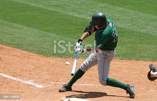 istock Baseball batter in green uniform hitting ball 184116635