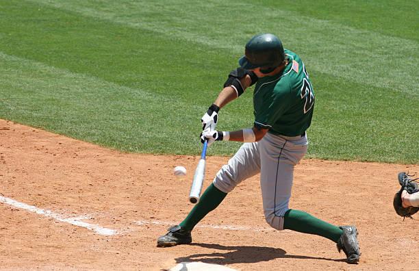 Baseball batter in green uniform hitting ball stock photo