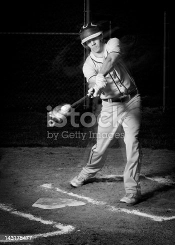 Amazing photo of a baseball ricocheting off of the batter's bat at home plate on a baseball diamond. Lime dust explodes off the ball after contact.